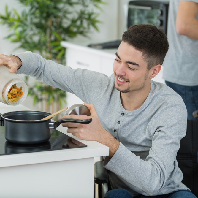 couple cooking together - man disabled on wheelchair